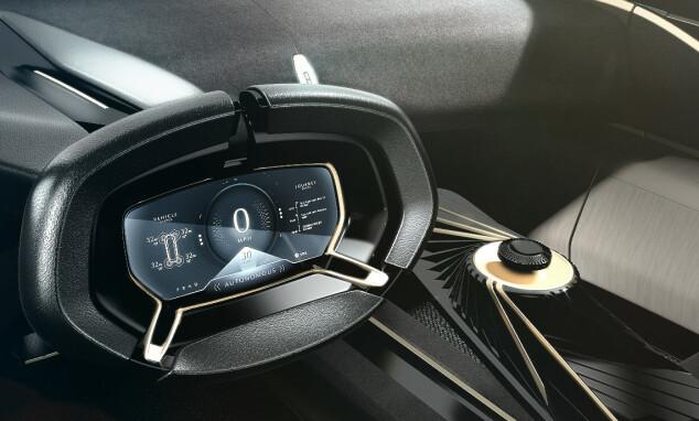 SVEVENDE NØKKEL: Midt i midtkonsollen svever den svarte nøkkelen over et beige platå ved hjelp av magnetisme. Foto: Aston Martin