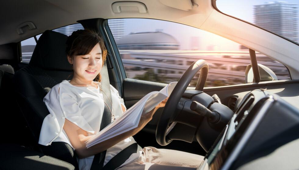 TRYGT: Forbrukere tror det er trygt å lese bok mens du kjører, dersom førerassistenter er slått på, viser ny amerikansk undersøkelse. Foto: Shutterstock