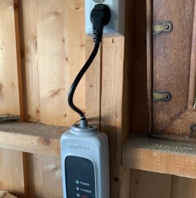 HENG OPP: Bruker du en såkalt «nødlader» for vanlig stikkontakt, skal den aldri henge i stikkontakten. La den hvile på plant underlag eller heng den opp på skrue, som her. Foto: Bjørn Eirik Loftås