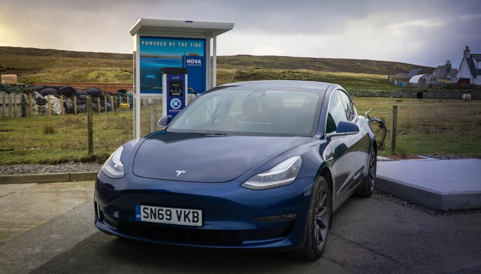 HAV BLIR STRØM: En Tesla Model 3 står og hurtiglader på Shetlands første tidevannsdrevne hurtigladestasjon. Ladehastigheten er maks 100 kW, og strømmen kommer fra én enkelt turbin. Foto: Nova Innovation
