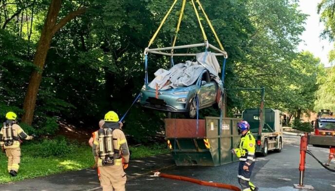 VANNBAD: Tidligere i sommer tok det fyr i batteriet i en parkert Hyundai Kona i Oslo. Her løftes bilen opp i en konteiner fylt med vann. Foto: Oslo brann- og redningsetat