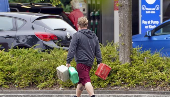 En mann kommer gående med tomme bensinkanner utenfor en bensinstasjon i Berkshire. Foto: Steve Parsons/PA via AP.